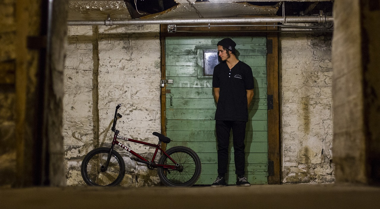 A man standing in front of a bicycle leaning against a wall