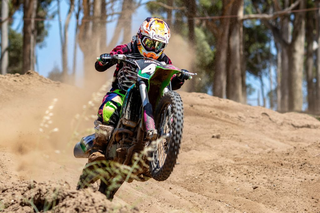 A man flying through the air while riding a motorcycle down a dirt road