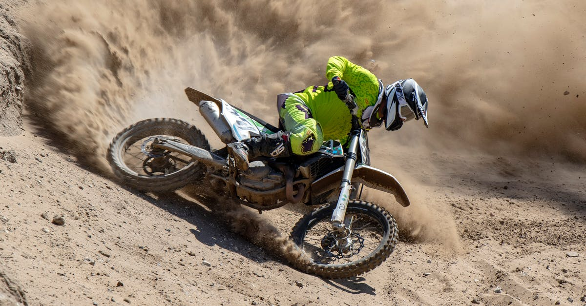 A person riding a motorcycle down a dirt road